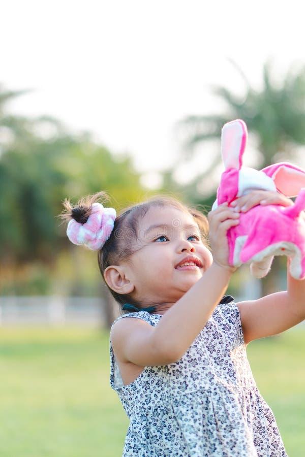 Das kleine Mädchen spielt eine Hundepuppe im Garten lizenzfreie stockfotografie