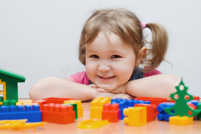 Das kleine Mädchen spielt Plastikblöcke lizenzfreie stockbilder