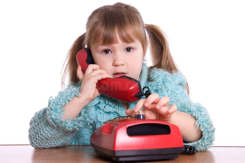 Das kleine Mädchen spricht durch Telefon stockfotografie