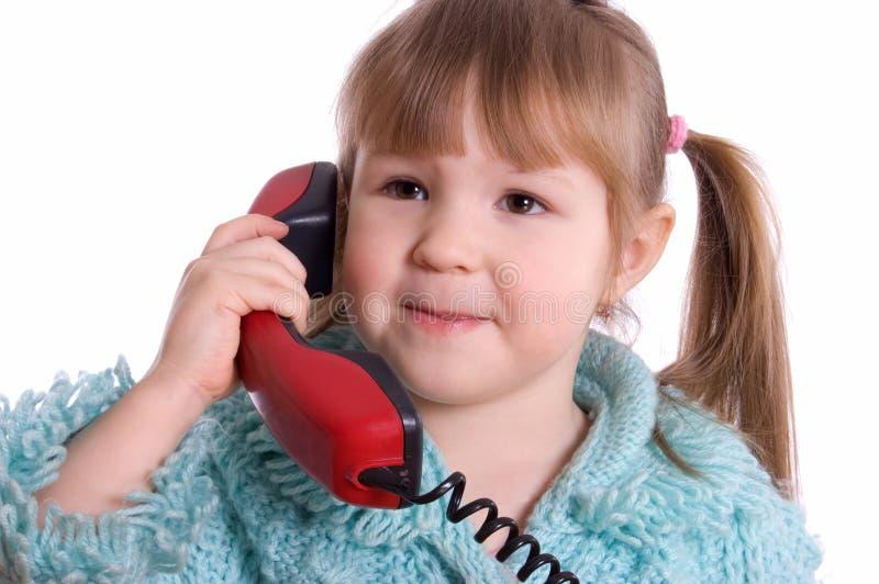 Das kleine Mädchen spricht durch Telefon stockfotos