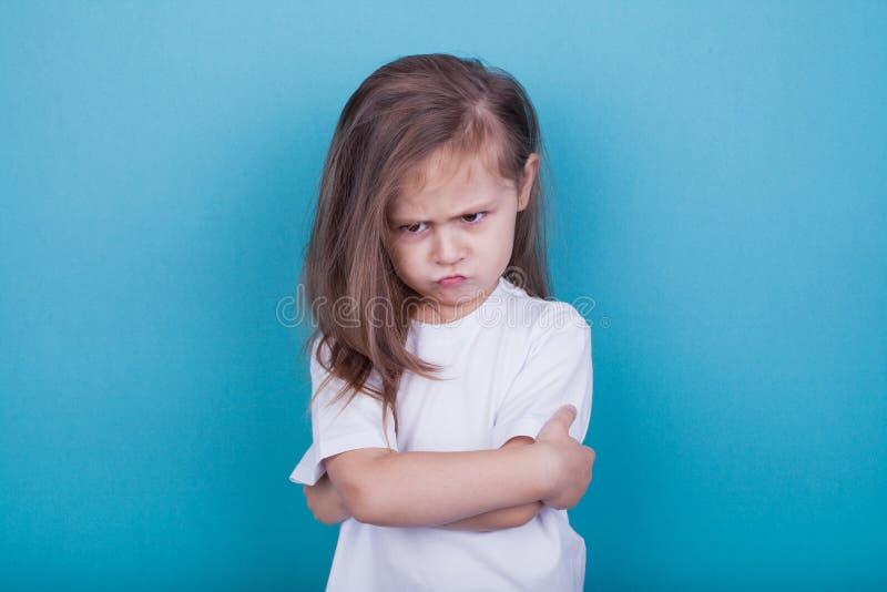 Das kleine Mädchen wurde beleidigt, indem man ihre Arme und die Stirn runzelnden Augenbrauen faltete lizenzfreie stockbilder