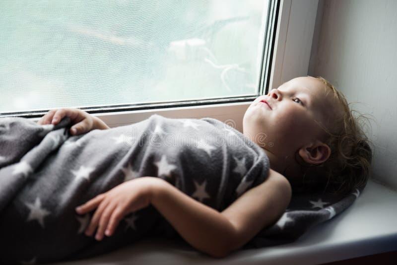 Das Kleinkind auf einem Fensterbrett stockfoto