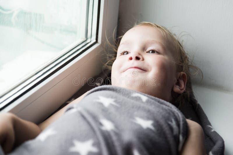 Das Kleinkind auf einem Fensterbrett lizenzfreie stockbilder