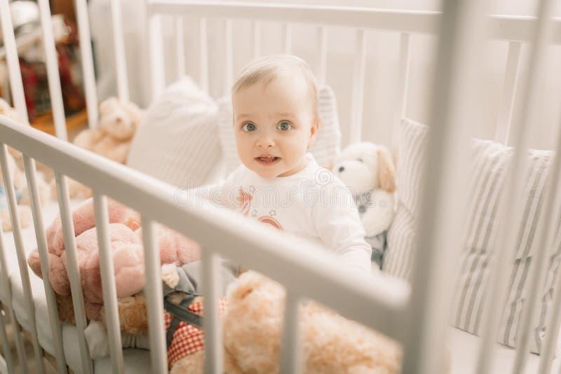 Das Kleinkind sitzt in einer Krippe und in den Spielen stockbild