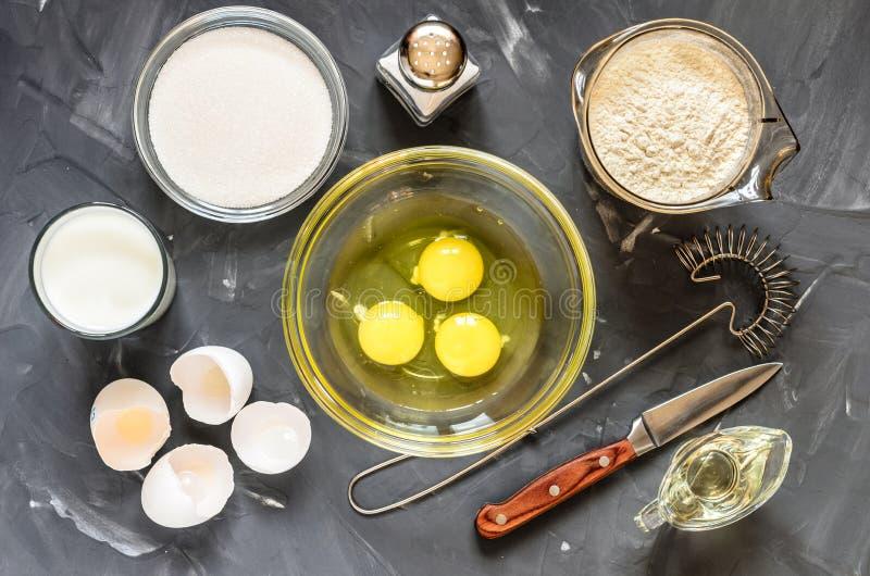 Das Kochen des Russen richtet Pfannkuchen an: Eier, Milch, Mehl, Butter, Salz lizenzfreie stockfotos