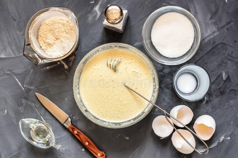 Das Kochen des Russen richtet Pfannkuchen an: Eier, Milch, Mehl, Butter, Salz stockfotografie