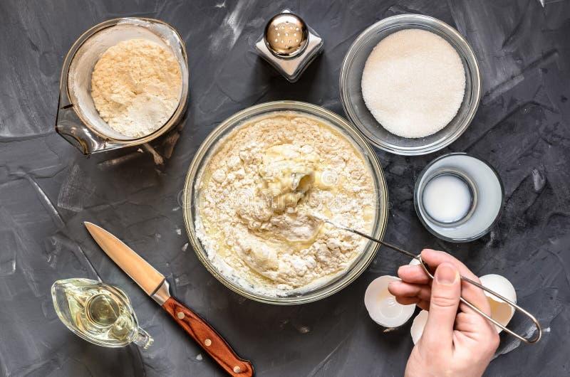 Das Kochen des Russen richtet Pfannkuchen an: Eier, Milch, Mehl, Butter, Salz Handrührender Teig lizenzfreie stockfotos