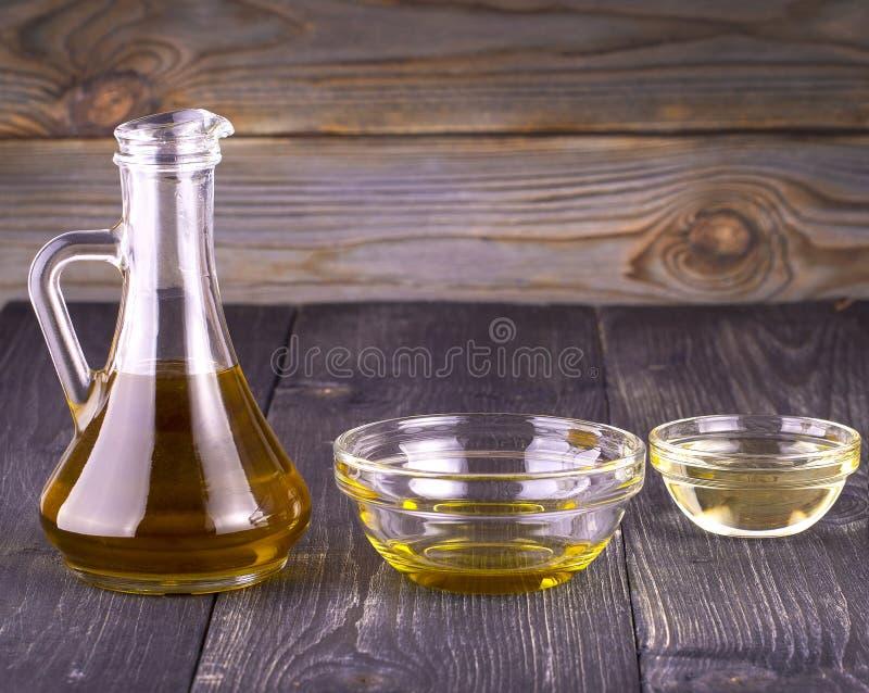 Das kochende Pflanzenöl in einer kleinen Glasschale und in einem Krug auf altem Holztisch stockfotografie