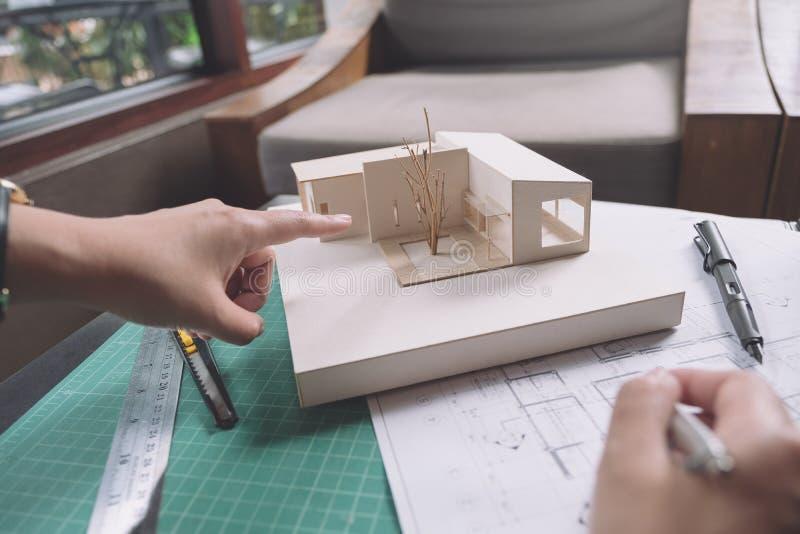 Das Kollegeteam von den Architekten, die auf Massenmodell mit Shopzeichenpapier und -laptop sich besprechen und zeigen stockfoto