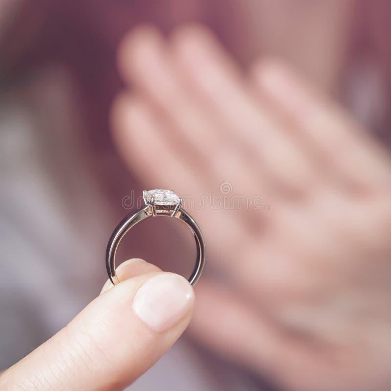 Das Konzept der Ablehnung der Verpflichtung oder der Hochzeit Das Mädchen hält einen Ring mit einem Diamanten lizenzfreies stockbild