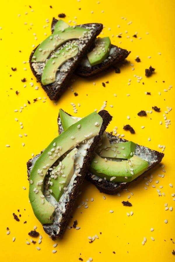 Das Konzept der gesunden Nahrung, des Roggenbrotsandwiches mit Avocado und des Käses auf einem gelben Hintergrund, vertikal stockbild