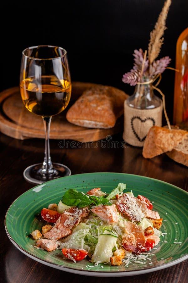 Das Konzept der italienischen Küche Caesar-Salat mit Lachs-, Kopfsalatmischung, Kirschtomaten und Parmesankäseparmesankäse Ein Gl lizenzfreies stockfoto