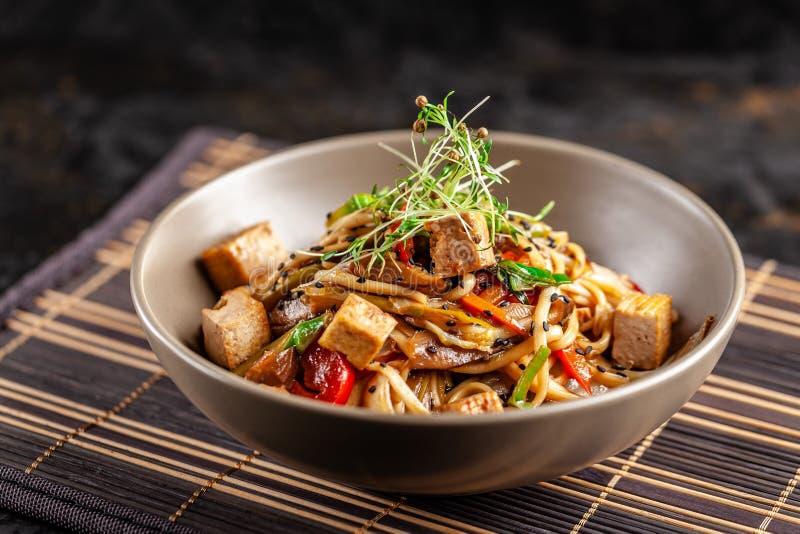 Das Konzept der japanischen Küche Chinesische Nudeln mit Huhn, gegrilltem Gemüse und Tofu in unagi Soße Dienende asiatische Telle lizenzfreie stockfotos
