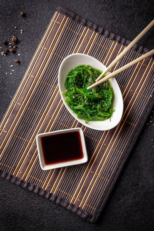 Das Konzept der japanischen und chinesischen Küche Chuka-Salat, gemacht von der Meerespflanze, vom indischen Sesam, vom Olivenöl  stockbild