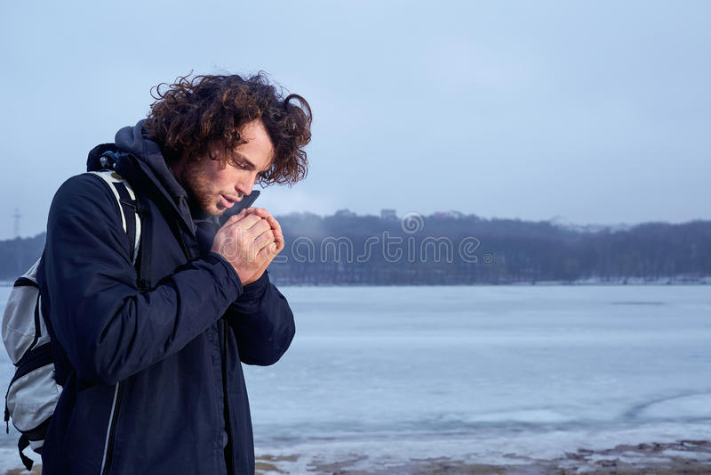 Das Konzept der Kälte, bereifen den gelockten behaarten jungen Mann, der seins wärmt stockbilder