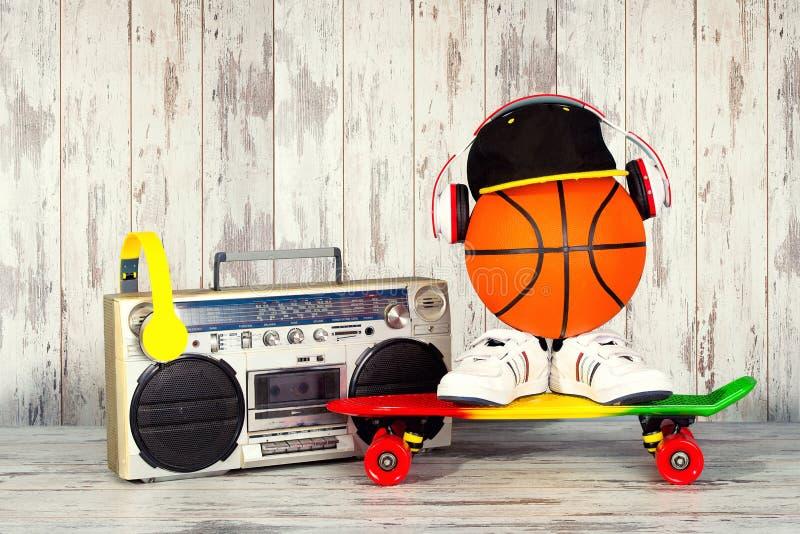 Das Konzept der Musik Hip-Hop-Art und -sports Weinleseaudiospieler mit Kopfhörern, moderner Kappe, Turnschuhen und Basketball b stockfotografie