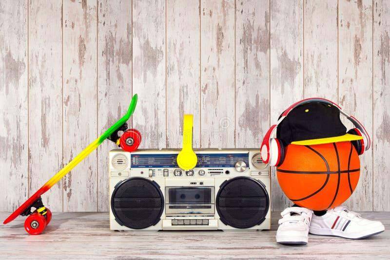 Das Konzept der Musik Hip-Hop-Art und -sports Weinleseaudiospieler mit Kopfhörern, moderner Kappe, Turnschuhen und Basketball b lizenzfreie stockfotografie