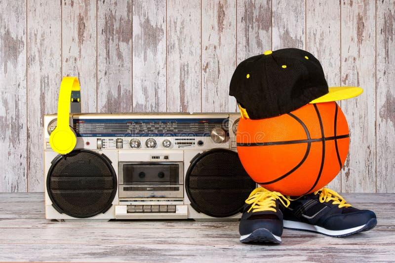 Das Konzept der Musik Hip-Hop-Art und -sports Weinleseaudiospieler mit Kopfhörern, moderner Kappe, Turnschuhen und Basketball b stockfotos