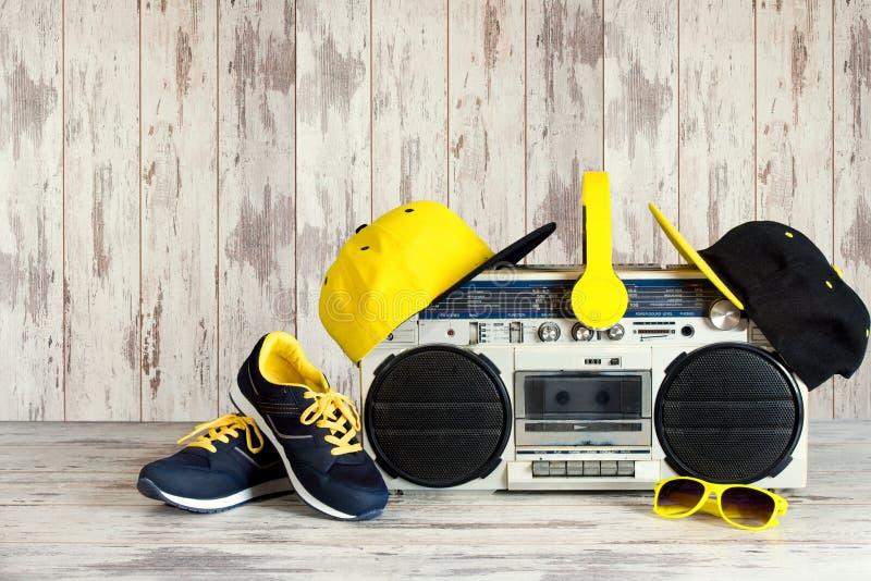 Das Konzept der Musik Hip-Hop-Art Weinleseaudiospieler mit Kopfhörern, moderner Kappe, Turnschuhen und Sonnenbrille lizenzfreies stockbild