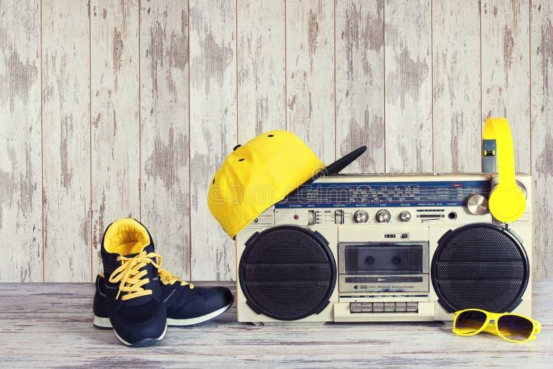 Das Konzept der Musik Hip-Hop-Art Weinleseaudiospieler mit Kopfhörern, moderner Kappe, Turnschuhen und Sonnenbrille lizenzfreie stockbilder