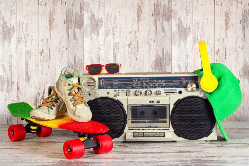 Das Konzept der Musik Hip-Hop-Art Weinleseaudiospieler mit Kopfhörern Skateboard, moderne Kappe und Sonnenbrille stockfotos