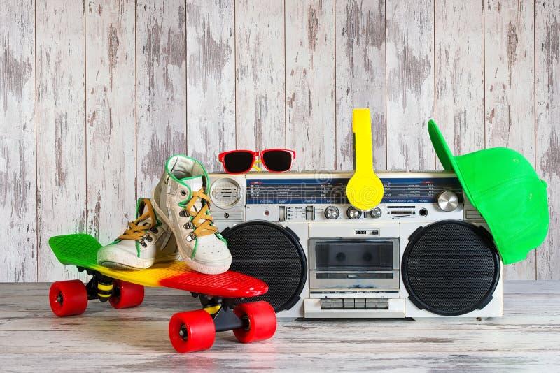 Das Konzept der Musik Hip-Hop-Art Weinleseaudiospieler mit Kopfhörern Skateboard, moderne Kappe und Sonnenbrille stockfoto
