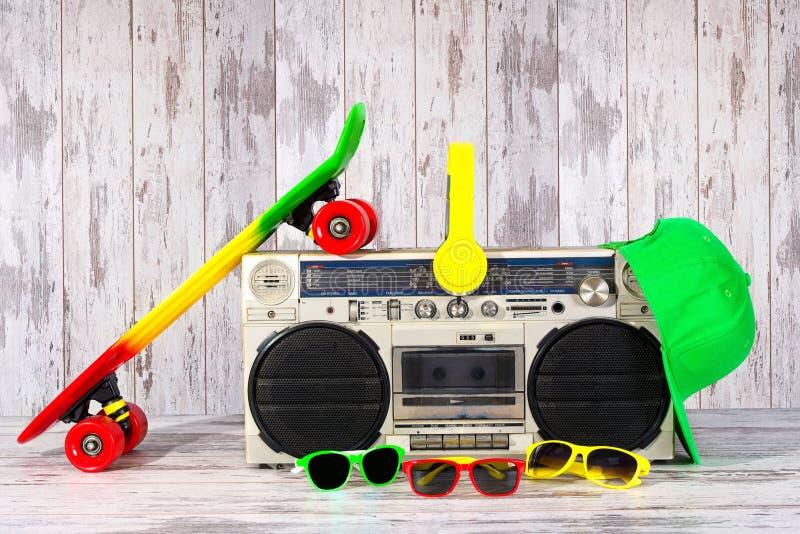 Das Konzept der Musik Hip-Hop-Art Weinleseaudiospieler mit Kopfhörern Skateboard, moderne Kappe und Sonnenbrille lizenzfreie stockbilder