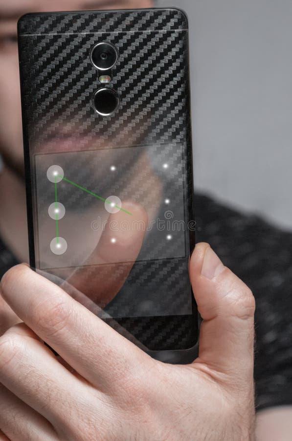 Das Konzept der Teilnehmerbezeichnung der Mann bewegt seinen Finger auf dem grafischen Schlüssel des Telefons zu Dateien entriege lizenzfreie stockfotos