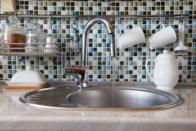 Das Konzept der Vergeudung des Wassers Öffnen Sie herausspritzendes Wasser des Küchenhahns lizenzfreie stockfotos