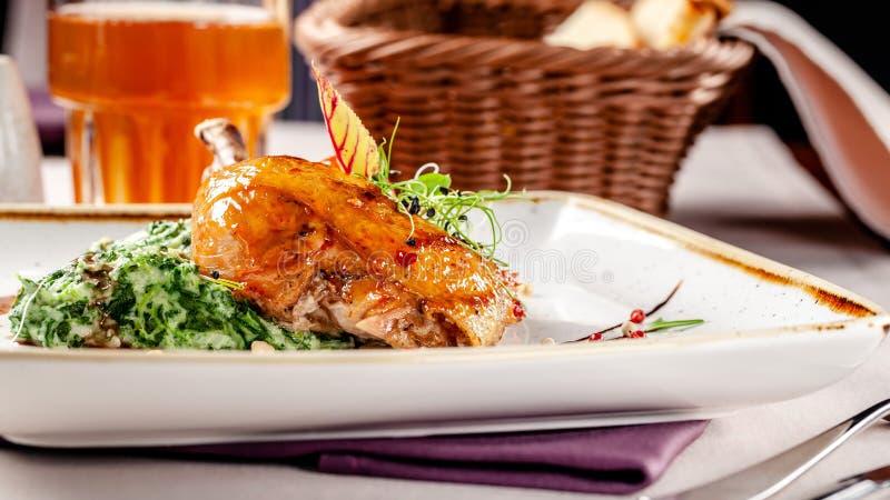 Das Konzept des Abendessens in einem japanischen Restaurant Spinatsgarnierung mit Sahne und glasig-glänzende Hühnerbeine in einer lizenzfreies stockfoto