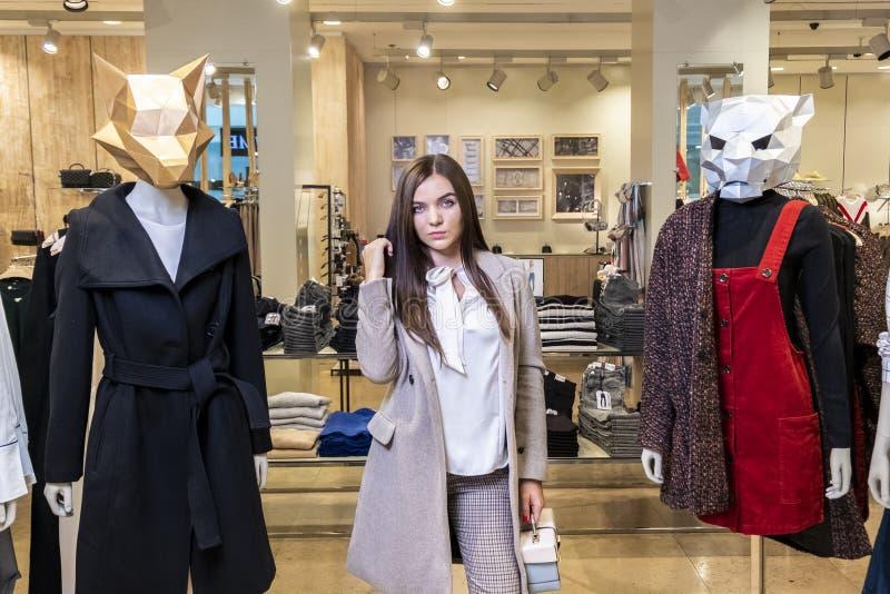 Das Konzept des Einkaufens und der Mode Schönes ernstes junges Brunettemädchen in einem Bekleidungsgeschäft nahe Mannequins mit T stockfotografie