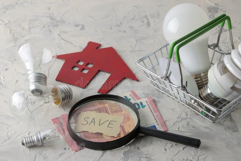 Das Konzept des Einsparungsstroms Geld, dekoratives Haus und verschiedene Glühlampen in einem Korb auf einem hellen Hintergrund stockbilder
