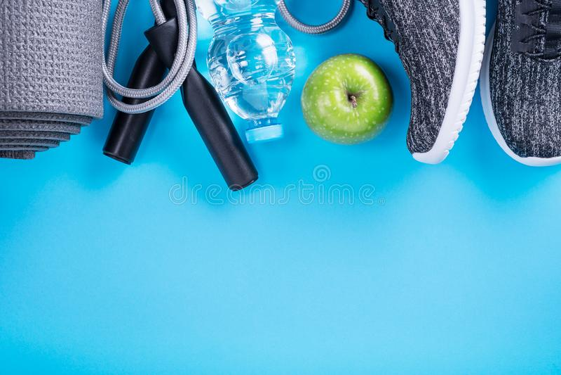 Das Konzept des gesunden Lebensstils Sportschuhe, Flasche Wasser, Apfel und Yogamatte mit Kopienraum auf blauem Hintergrund Übung stockfotografie