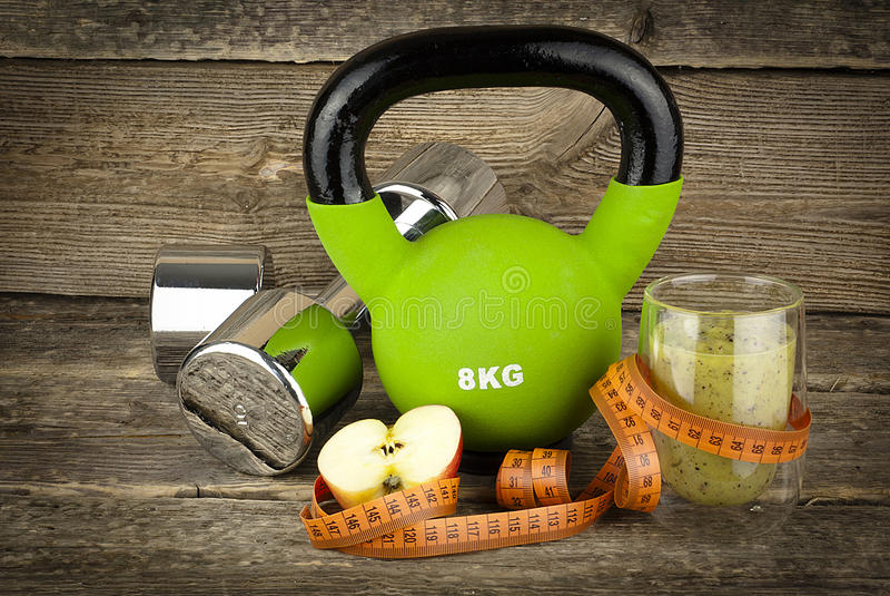 Das Konzept des Gewichtsverlusts, des dumbell und des kettlebell lizenzfreies stockbild