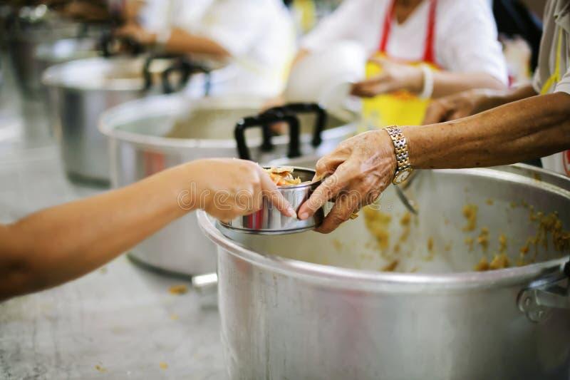 Das Konzept des Spendens der Nahrung zu den Armen, um Nahrung von den Händen von denen zu empfangen, die wohlhabend sind stockfoto