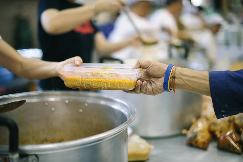 Das Konzept des Spendens der Nahrung zu den Armen, um Nahrung von den Händen von denen zu empfangen, die wohlhabend sind stockbilder