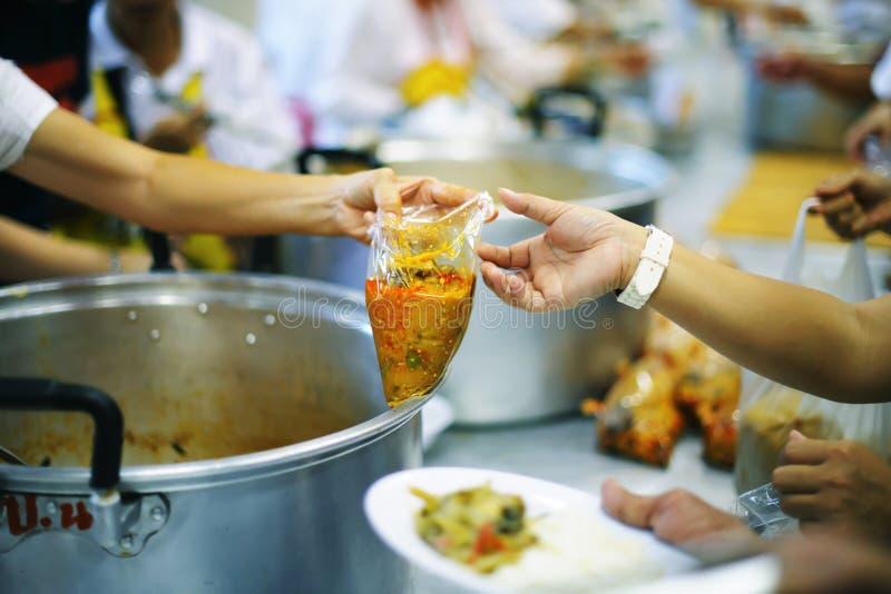 Das Konzept des Spendens der Nahrung zu den Armen, um Nahrung von den Händen von denen zu empfangen, die wohlhabend sind lizenzfreies stockfoto