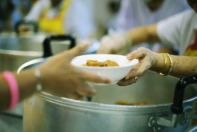 Das Konzept des Spendens der Nahrung zu den Armen, um Nahrung von den Händen von denen zu empfangen, die wohlhabend sind stockfotos