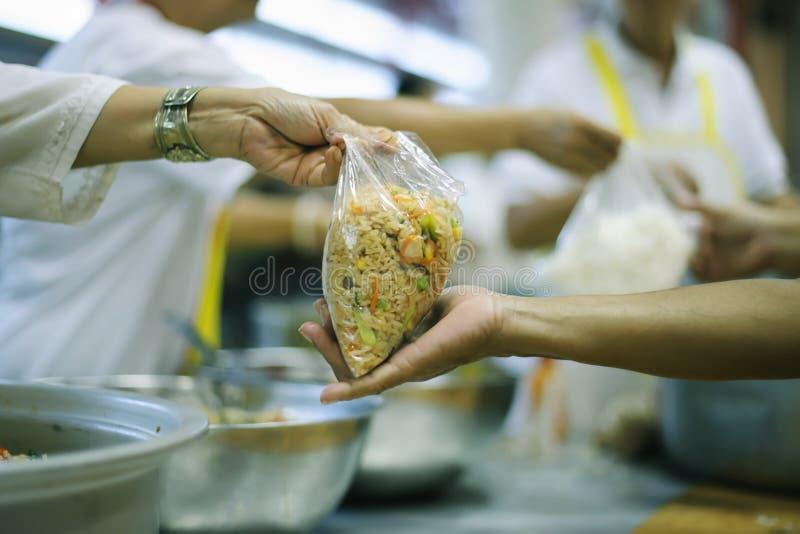 Das Konzept des Spendens der Nahrung zu den Armen, um Nahrung von den Händen von denen zu empfangen, die wohlhabend sind lizenzfreies stockbild
