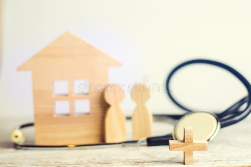 Das Konzept von Familienmedizin und -versicherung Stethoskop und Familie auf einem hölzernen Hintergrund stockbilder