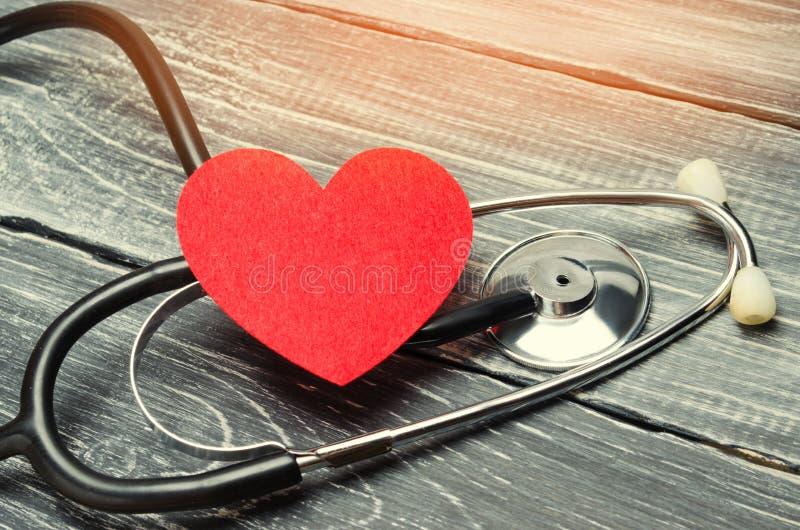 Das Konzept von Familienmedizin und -versicherung Stethoskop und Herz auf einem hölzernen Hintergrund stockbild