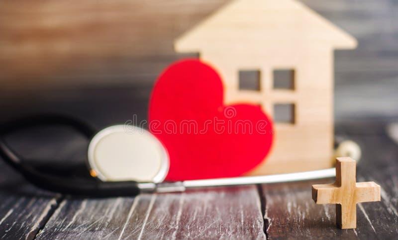 Das Konzept von Familienmedizin und -versicherung Stethoskop und Herz auf einem schwarzen hölzernen Hintergrund lizenzfreie stockbilder