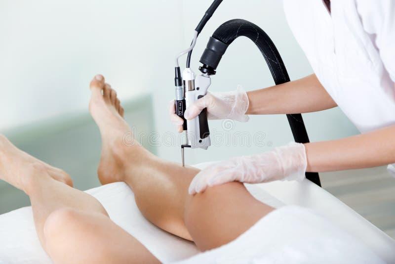 Das Kosmetiker ` s übergibt das Entfernen des Beinhaares mit einem Laser zu ihrem Kunden im Schönheitssalon stockbild