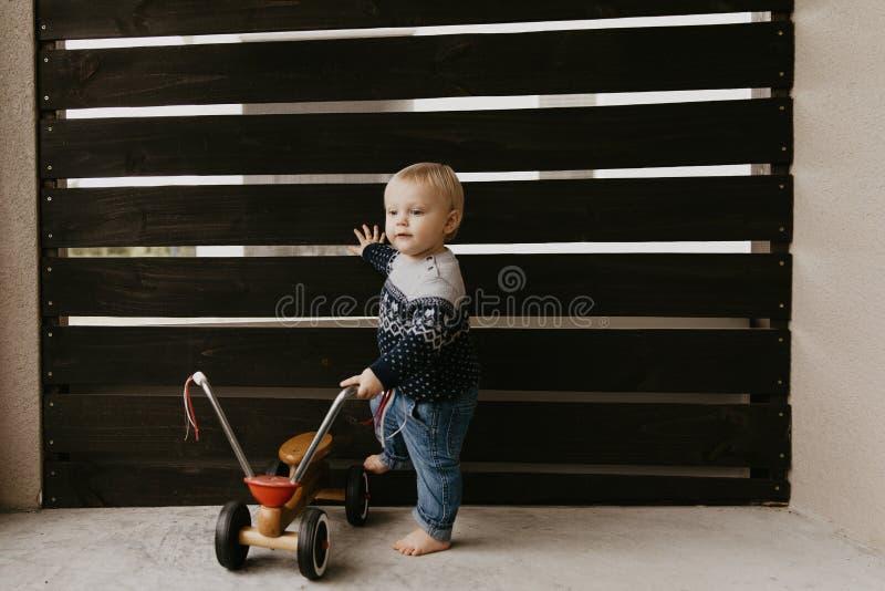 Das kostbare entzückende nette kleine blonde Baby-Kleinkind-Jungen-Kind, das draußen auf hölzernem Toy Bicycle Scooter Mobile Smi stockfotos