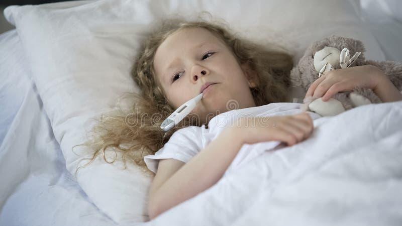 Das kranke kleine M?dchen, das im Bett traurig ist mit Thermometer im Mund liegt, Kind fing kaltes lizenzfreies stockbild