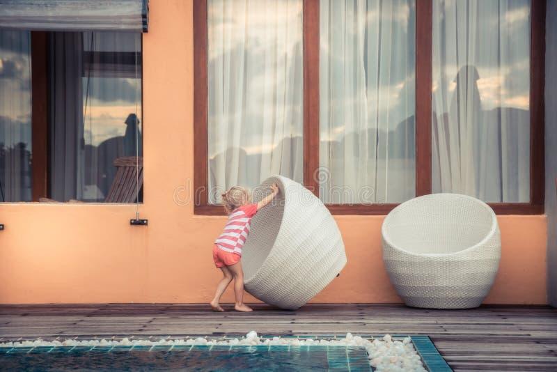 Das kreative kleines Kinderversuchen stellen gro?en Stuhl des modernen Entwurfs symbolisieren kreative Kunstentwurfsentwicklung i lizenzfreie stockfotos