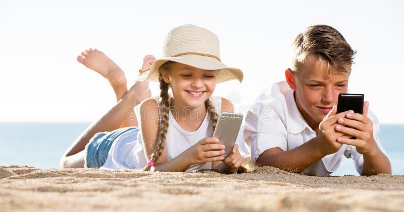 Das Lächeln scherzt auf Strand mit Telefon in den Händen lizenzfreies stockfoto