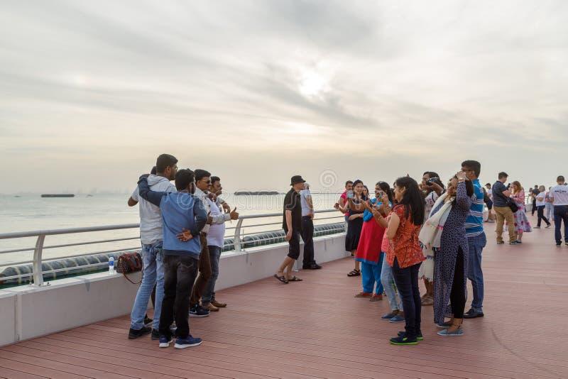Das Lächeln und die glücklichen Touristen werden auf der Ufergegend am Abend fotografiert stockfotografie