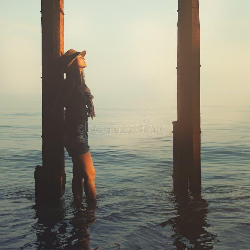 Das lächelnde Hippie-Mädchen, das auf ein Meer geht, setzen auf den Strand stockbild