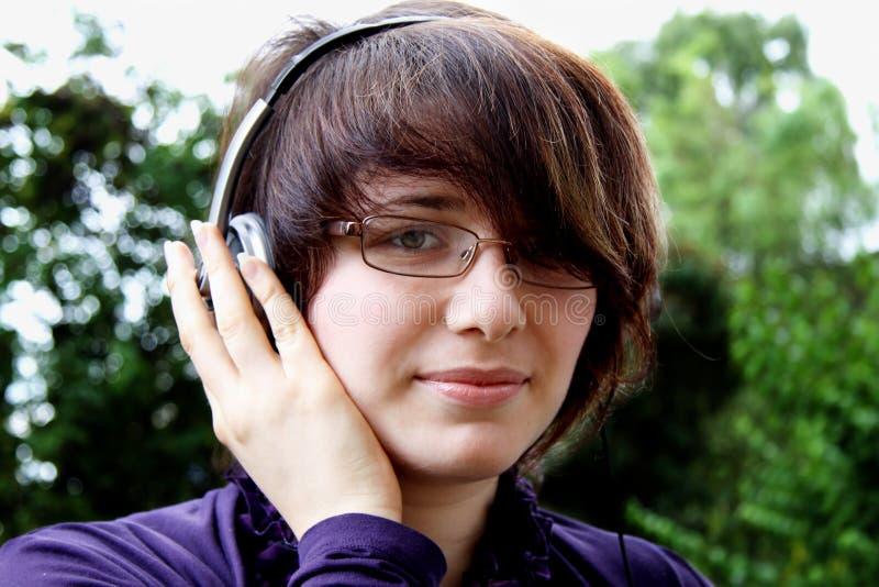 Das lächelnde Mädchen hört Musik lizenzfreie stockfotos